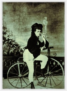 Velocipede and smoking woman with pointy boots, puffy pants and specs